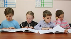 Four children sit at a table, reading a book and turn the pages Stock Footage