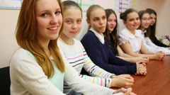 Seven young girls sitting at the table and looking at the camera Stock Footage