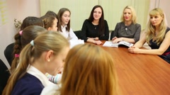 Three teachers sitting in front of seven schoolgirls at table Stock Footage