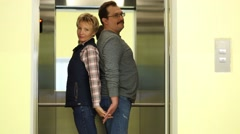 Man and woman are standing back to back holding hands in elevator Stock Footage