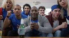 4K Group of friends watching sports game on TV celebrate when team score - stock footage