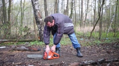 The man pulling the rope and trying to start a chainsaw Stock Footage