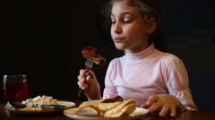 The girl eating baked chicken wings in a restaurant Stock Footage