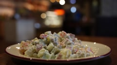Plate with delicious Olivier Salad on a table in a cafe Stock Footage