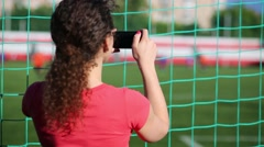 The woman stands behind net and shoots on the phone a football game Stock Footage