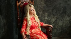 Girl with long blond hair in a red dress sitting on a chair Stock Footage