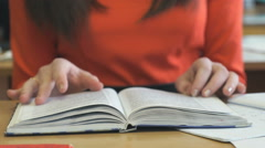 Young girl sits and flips through a book tutorial - stock footage