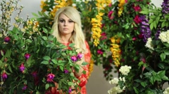 Beautiful girl with long blond hair is walking among flowers Stock Footage
