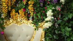 Luxurious white chair surrounded by colorful flowers Stock Footage