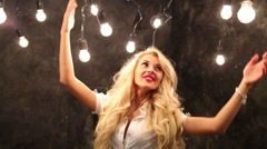A woman is standing in room with lots of lights and raises hands up Stock Footage