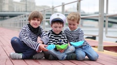 Three boys sit on the docks and playing with paper boats Stock Footage