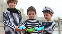 Three boys in vests playing with paper boats on embankment Stock Footage