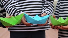 Three paper boats in the hands of the boys in vests Stock Footage