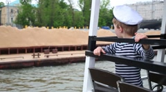 Boy in cap and vest on boat looks at barge with sand floats beside Stock Footage