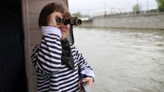 Boy in vest stands on deck of boat and looking through binoculars Stock Footage
