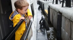 Little boy in yellow jacket looking at boat approaching pier Stock Footage