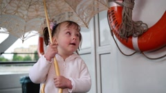 Little girl standing on the deck of the pleasure boat with an umbrella Stock Footage
