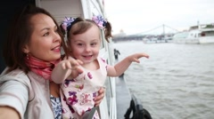 Mother and daughter standing on the deck of a pleasure boat Stock Footage