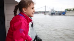 A girl in  jacket looks at the city standing on a pleasure boat Stock Footage