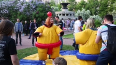 People watch two girls fighting in sumo costumes Stock Footage