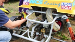 Man spins spring at a race car before competition at outdoor track Stock Footage