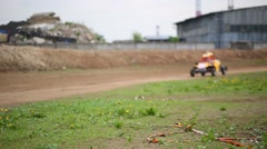 Bright yellow racing car driven by a child riding a dirt track Stock Footage
