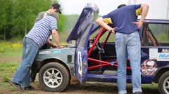 Men look around the race car on the outdoors track Stock Footage