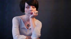 Serious woman with short hair sitting leaning on her elbow Stock Footage