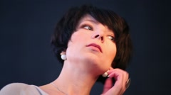 Close-up of a young woman with short hair straightens hairstyle - stock footage
