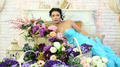 Woman rests on arm of chair and then rises surrounded by flowers Stock Footage