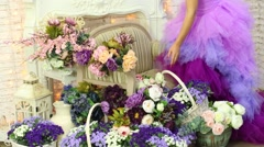 Woman in a magnificent dress picks up a basket of flowers Stock Footage