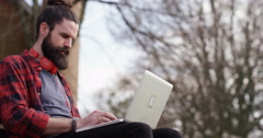 4K Man enjoying quiet time in the park,working on laptop with bicycle beside him Stock Footage