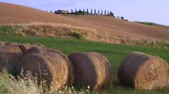 Tuscan landscape, house circled by cypress trees and bales of hay, wide shot - stock footage