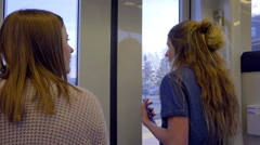 Teen Girls Stand By Train Doors And Look Out Windows At City Views Passing By Stock Footage
