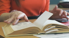 Schoolgirl sits at a desk, leafing through a book Stock Footage