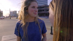 Teens Chat While They Wait To Cross City Street, Girl Checks Her Phone Stock Footage