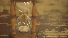Hourglass on old table Stock Footage
