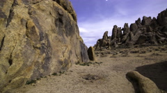 3axis MoCo Astro Time Lapse of Stars over Moonlit Rocky Desert -Tilt Up- Stock Footage