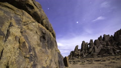3axis MoCo Astro Time Lapse of Stars over Moonlit Rocky Desert -Tilt Down- - stock footage