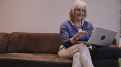 Senior adult woman at home purchasing on laptop - stock footage