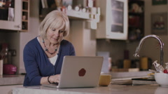 Senior adult woman at home shopping online Stock Footage