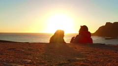 Two people talking at sunset at the ocean Stock Footage