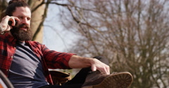 4K Cheerful casual man enjoying quiet time outdoors & chatting on mobile phone Stock Footage