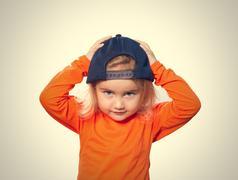 Little Funny girl in baseball cap and orange blouse - stock photo