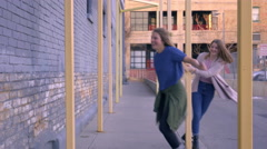 Playful Teens Hide And Dance Around Yellow Poles On Sidewalk In Urban Setting Stock Footage