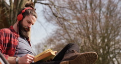 4K Man with bicycle relaxing in nature, reading a book & listening to music Stock Footage