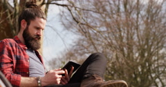 4K Young casual man enjoying quiet time in nature & looking at smartphone Stock Footage