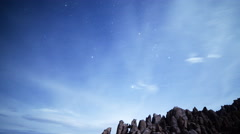 Astrophotography Time Lapse of Stars over Moonlit Rock Formation -Tilt Down- - stock footage