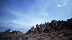 Astrophotography Time Lapse of Stars over Moonlit Rock Formation -Pan Right- - stock footage