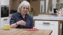 Senior Adult Woman opening Valentine's Day Card at kitchen table Stock Footage